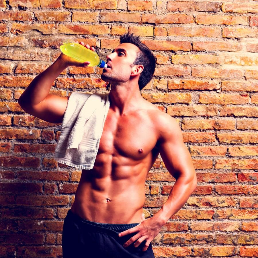 Мужчина пьет энергетический напиток в спортзале