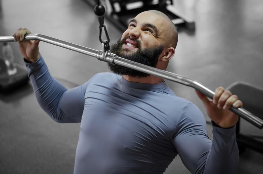 Мужчина с бородой делает тягу нижнего блока в спортзале